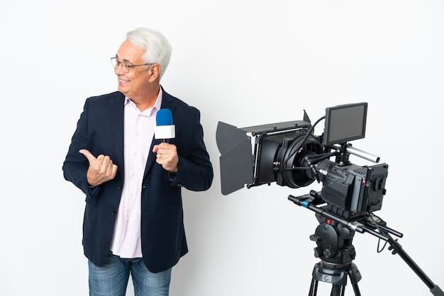 Repórter brasileiro de meia-idade segurando um microfone e relatando notícias isoladas em fundo branco apontando para o lado para apresentar um produto
