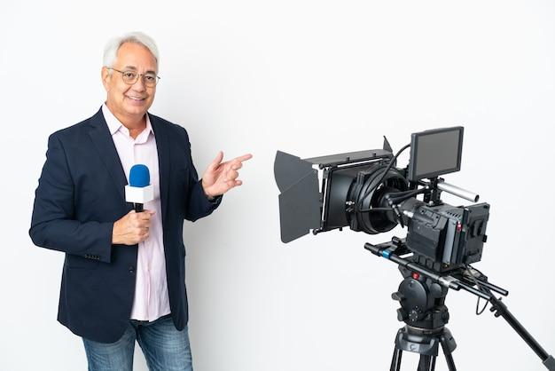 Repórter brasileiro de meia-idade segurando um microfone e relatando notícias isoladas em um fundo branco apontando o dedo para o lado