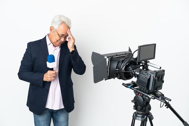 Repórter brasileiro de meia-idade segurando um microfone e relatando notícias isoladas em um fundo branco com dor de cabeça