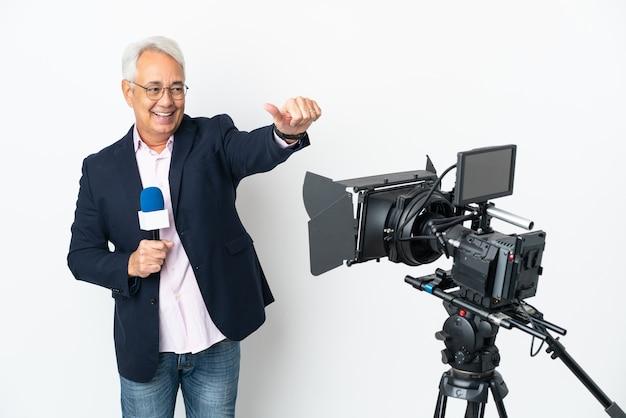 Repórter brasileiro de meia-idade segurando um microfone e relatando notícias isoladas em um fundo branco com gesto de polegar para cima