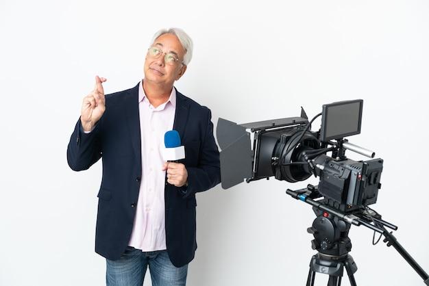 Repórter brasileiro de meia-idade segurando um microfone e relatando notícias isoladas em um fundo branco com os dedos se cruzando e desejando o melhor