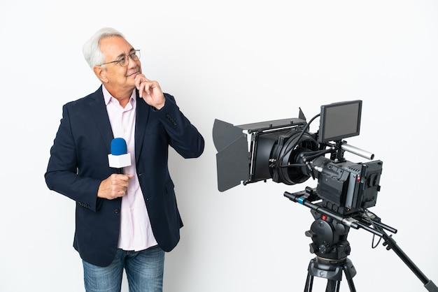 Repórter brasileiro de meia-idade segurando um microfone e relatando notícias isoladas em um fundo branco e olhando para cima