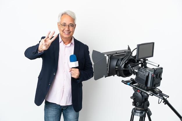 Repórter brasileiro de meia-idade segurando um microfone e relatando notícias isoladas em um fundo branco feliz e contando três com os dedos