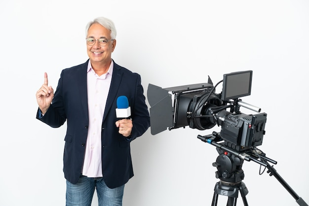 Repórter brasileiro de meia-idade segurando um microfone e relatando notícias isoladas em um fundo branco mostrando e levantando o dedo em sinal dos melhores