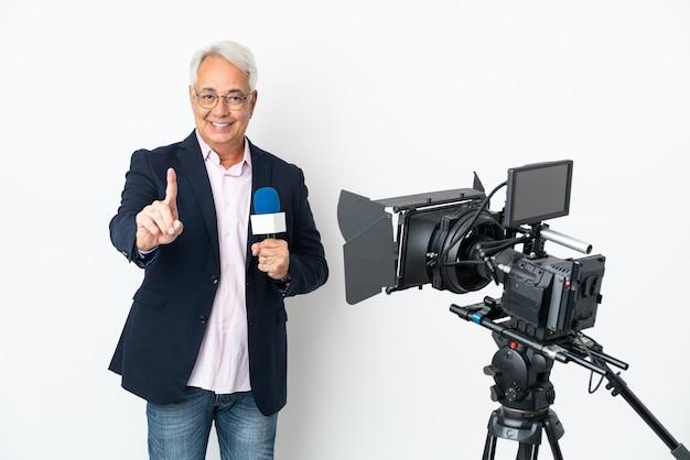 Repórter brasileiro de meia-idade segurando um microfone e relatando notícias isoladas em um fundo branco mostrando e levantando um dedo