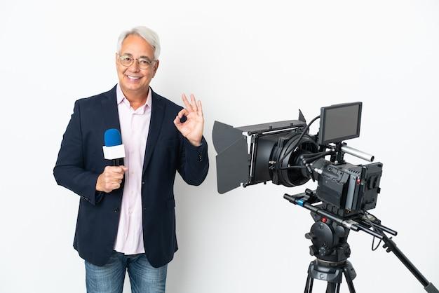 Repórter brasileiro de meia-idade segurando um microfone e relatando notícias isoladas em um fundo branco mostrando sinal de ok com os dedos