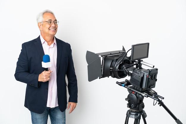 Repórter brasileiro de meia-idade segurando um microfone e relatando notícias isoladas em um fundo branco pensando uma ideia olhando para cima