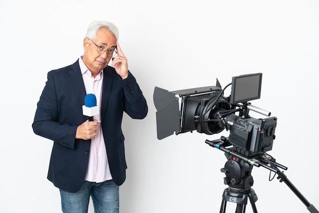 Repórter brasileiro de meia-idade segurando um microfone e relatando notícias isoladas em um fundo branco pensando uma ideia