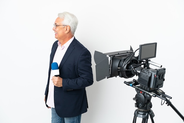 Repórter brasileiro de meia-idade segurando um microfone e relatando notícias isoladas em um fundo branco rindo em posição lateral