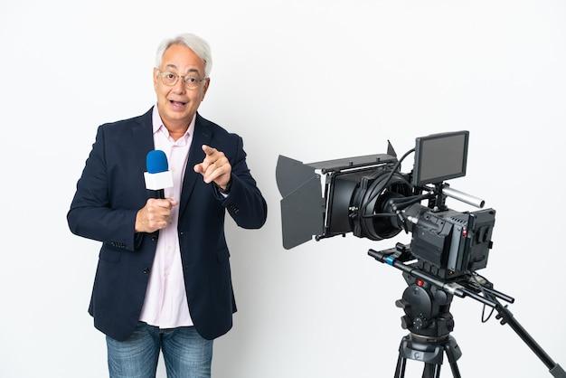 Repórter brasileiro de meia-idade segurando um microfone e relatando notícias isoladas em um fundo branco surpreso e apontando para frente