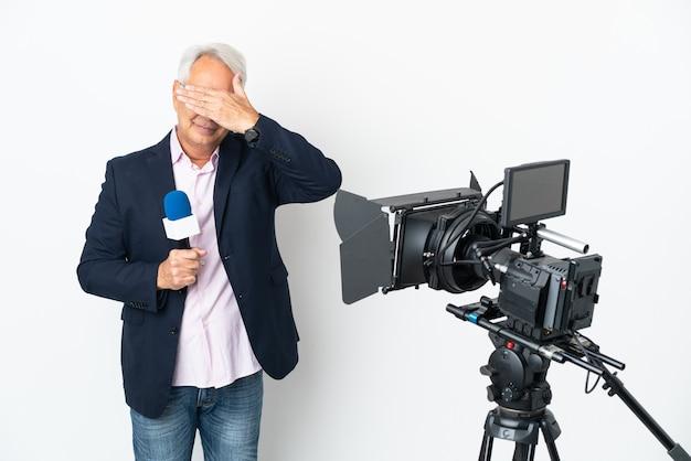 Repórter brasileiro de meia idade segurando um microfone e relatando notícias isoladas no fundo branco, cobrindo os olhos com as mãos. não quero ver nada