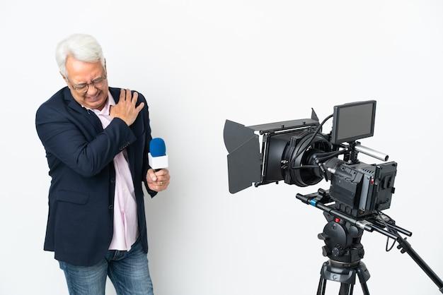 Repórter brasileiro de meia-idade segurando um microfone e relatando notícias isoladas no fundo branco sofrendo de dores no ombro por ter feito esforço