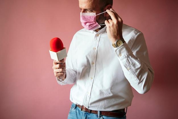 Repórter colocando máscara e usando microfone na parede rosa