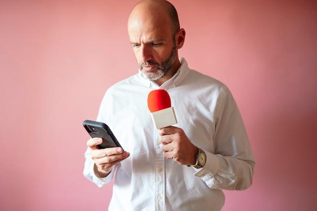 Repórter com smartphone e microfone com fundo rosa