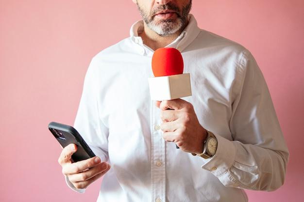 Repórter com smartphone e microfone com parede rosa