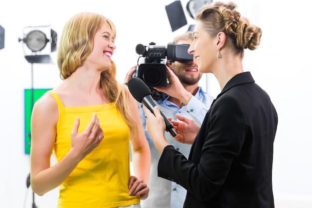 Repórter e cinegrafista filmam uma entrevista