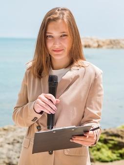 Repórter em pé junto ao mar