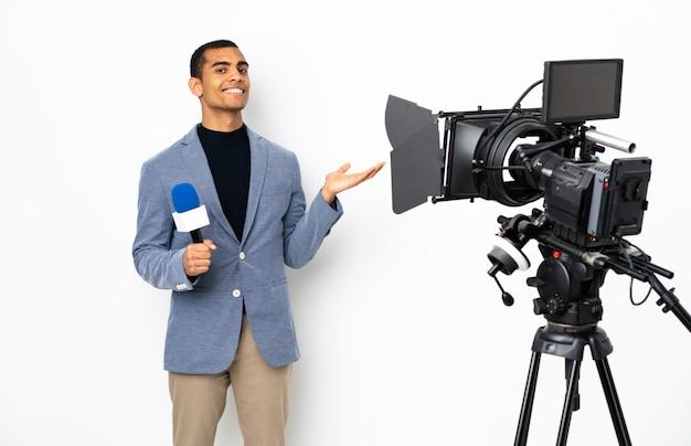 Repórter homem afro-americano segurando um microfone e reportando notícias sobre parede branca isolada, estendendo as mãos para o lado por convidar para vir
