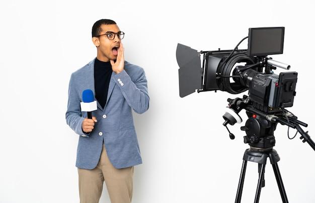 Repórter homem afro-americano segurando um microfone e reportando notícias sobre parede branca isolada sussurrando algo com gesto de surpresa enquanto olha para o lado