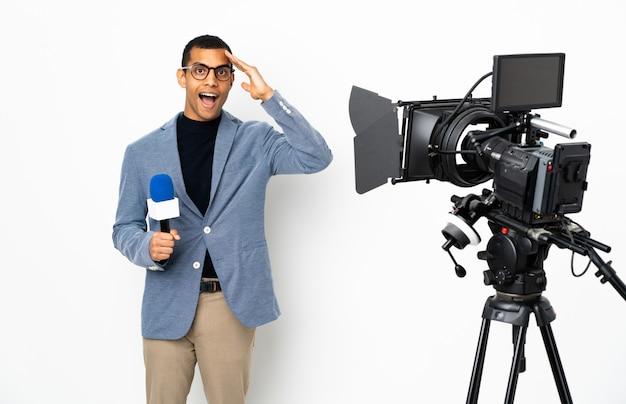 Repórter homem afro-americano segurando um microfone e reportando notícias sobre uma parede branca isolada percebeu algo e pretendia a solução