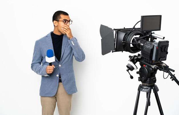 Repórter homem afro-americano segurando um microfone e reportar notícias sobre parede branca isolada, cobrindo a boca e olhando para o lado