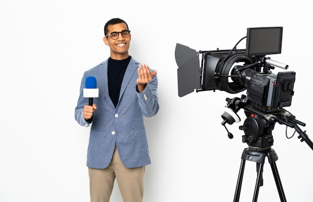 Repórter homem afro-americano segurando um microfone e reportar notícias sobre parede branca isolada, convidando para vir com a mão. feliz que você veio