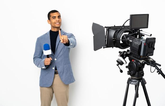 Repórter homem afro-americano segurando um microfone e reportar notícias sobre parede branca isolada, mostrando e levantando um dedo