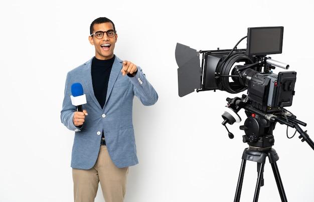 Repórter homem afro-americano segurando um microfone e reportar notícias sobre parede branca isolada surpreendeu e apontando a frente