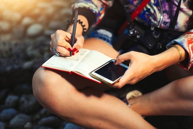 Repórter jornalista com câmera toma notas em um caderno