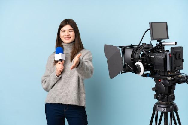 Repórter jovem mulher segurando um microfone e relatar notícias aperto de mão depois de um bom acordo