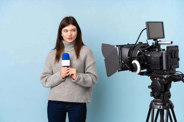Repórter jovem mulher segurando um microfone e reportando notícias em pé e olhando para o lado
