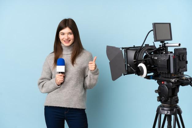 Repórter jovem mulher segurando um microfone e reportar notícias dando um polegar para cima gesto