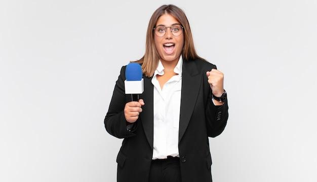 Repórter jovem se sentindo chocada, animada e feliz, rindo e comemorando o sucesso, dizendo uau!