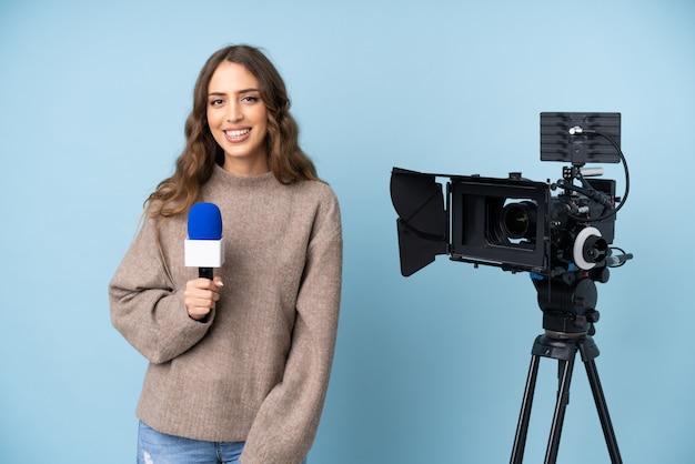 Repórter jovem segurando um microfone e relatando notícias rindo