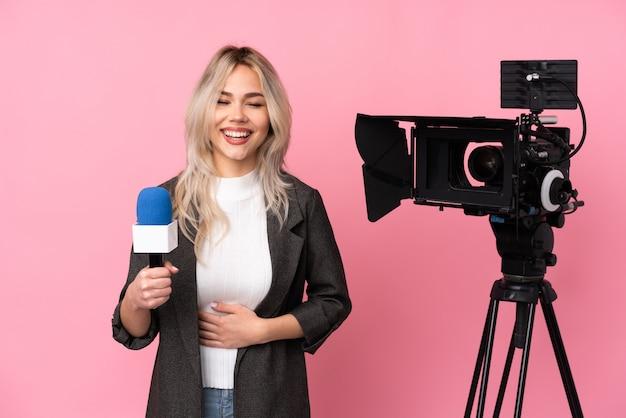 Repórter mulher com uma câmera rindo