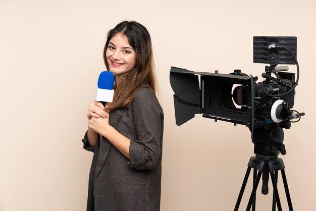 Repórter mulher segurando um microfone e relatando notícias sobre parede rindo