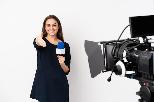Repórter mulher segurando um microfone e reportando notícias em branco, apertando as mãos para fechar um bom negócio