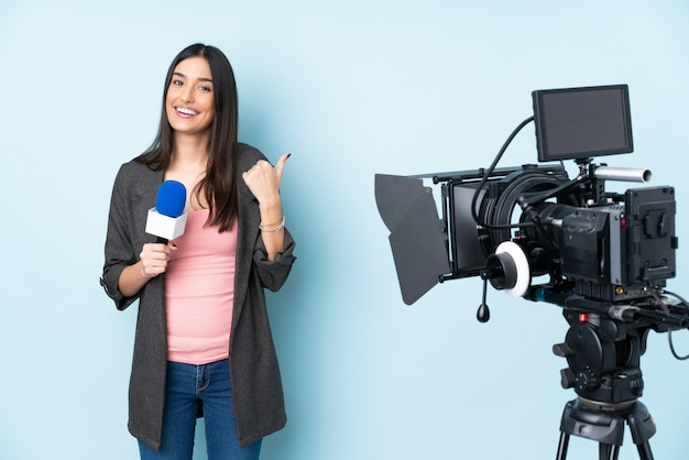 Repórter mulher segurando um microfone e reportando notícias isoladas na parede azul com polegares para cima gesto e sorrindo