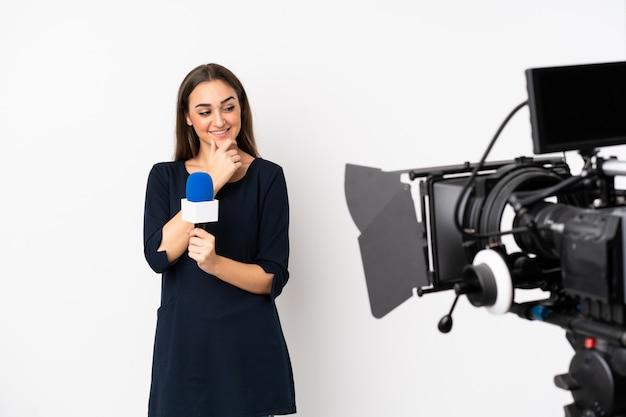 Repórter mulher segurando um microfone e reportando notícias isoladas na parede branca, olhando para o lado