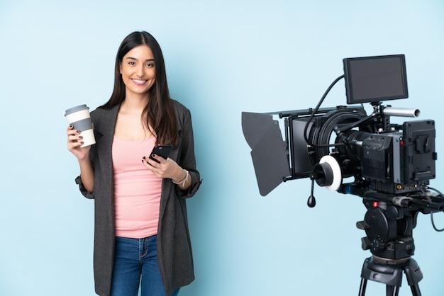 Repórter mulher segurando um microfone e reportando notícias na parede azul segurando café para tirar e um celular