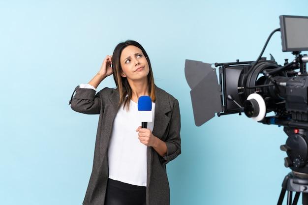 Repórter mulher segurando um microfone e reportando notícias sobre parede azul com expressão de rosto confuso
