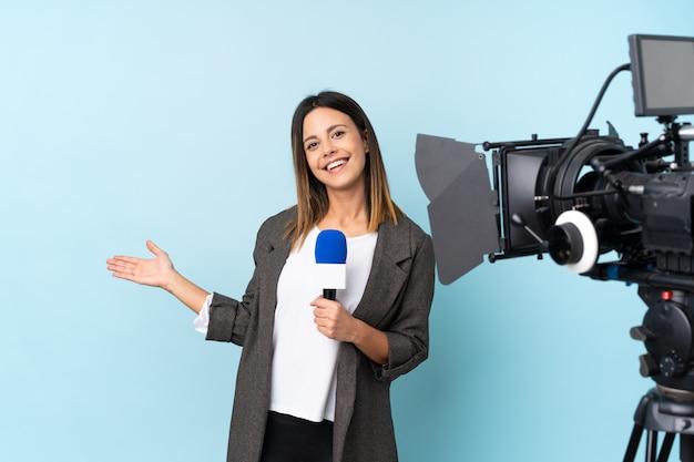 Repórter mulher segurando um microfone e reportando notícias sobre parede azul isolada, estendendo as mãos para o lado para convidar para vir