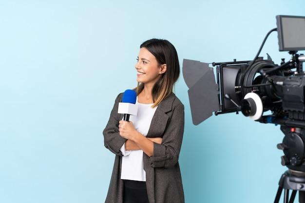 Repórter mulher segurando um microfone e reportando notícias sobre parede azul isolada, olhando para o lado