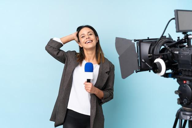 Repórter mulher segurando um microfone e reportando notícias sobre parede azul rindo