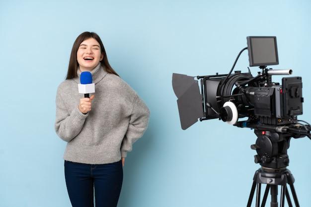 Repórter mulher segurando um microfone e reportando notícias sobre parede azul