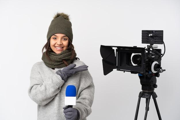 Repórter mulher segurando um microfone e reportando notícias sobre parede branca, apresentando uma idéia enquanto olha sorrindo para