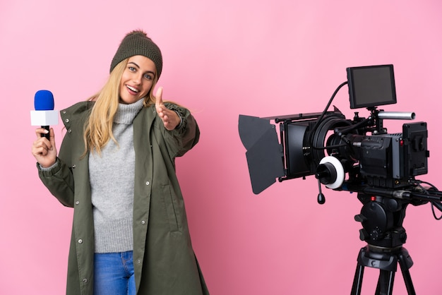 Repórter mulher segurando um microfone e reportando notícias sobre parede rosa apertando as mãos para fechar um bom negócio