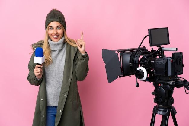 Repórter mulher segurando um microfone e reportando notícias sobre parede rosa apontando para cima uma ótima idéia