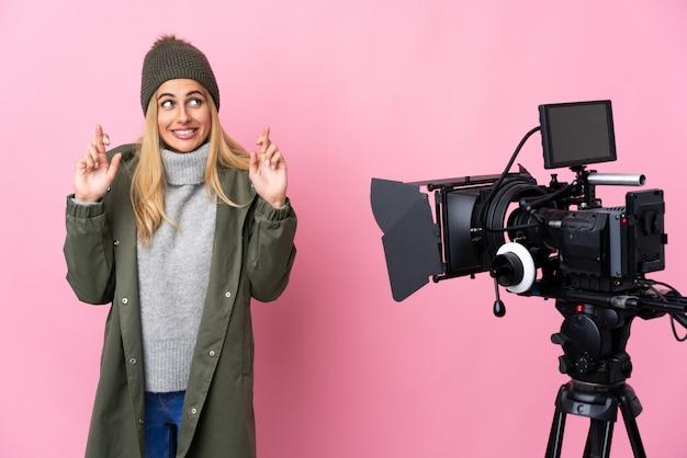 Repórter mulher segurando um microfone e reportando notícias sobre parede rosa com dedos cruzando e desejando o melhor