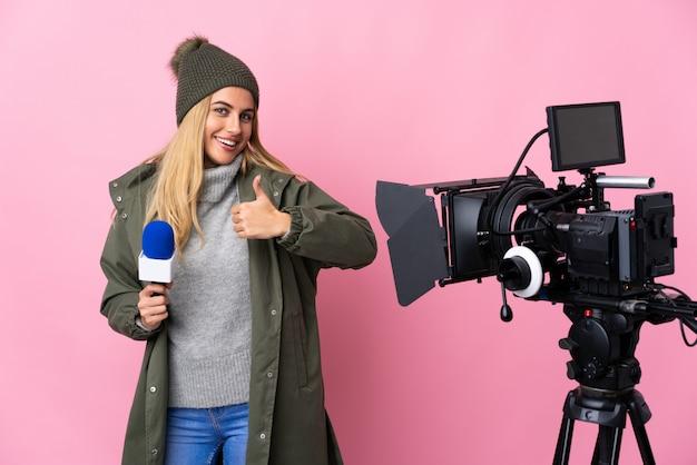 Repórter mulher segurando um microfone e reportando notícias sobre parede rosa dando um polegar para cima gesto